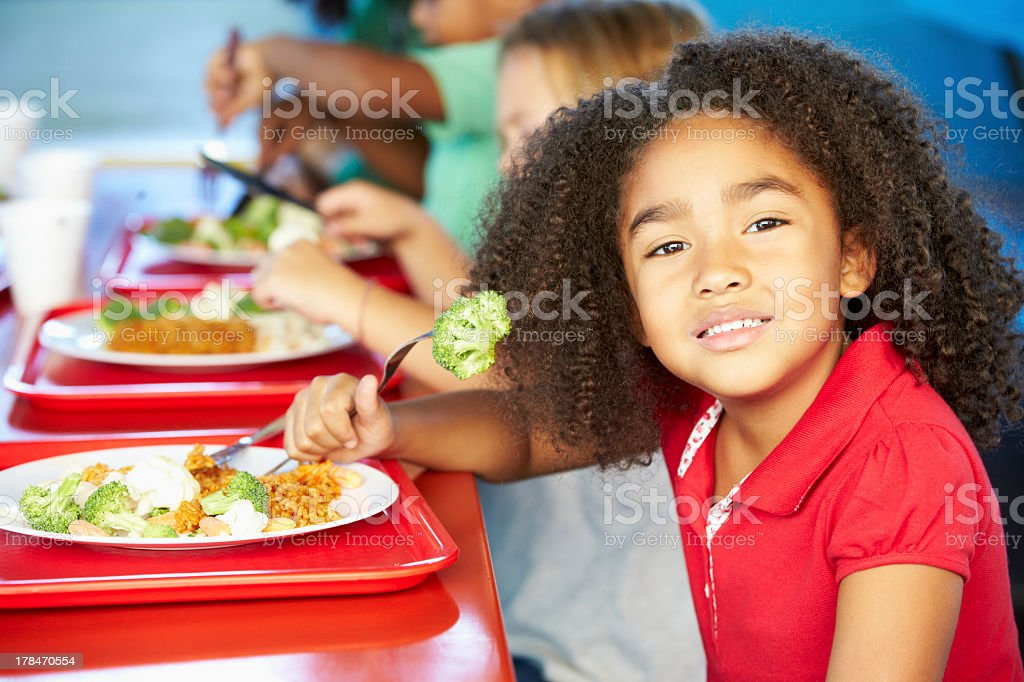 Smiling public school girl eating healthy vegetable lunch stock photo