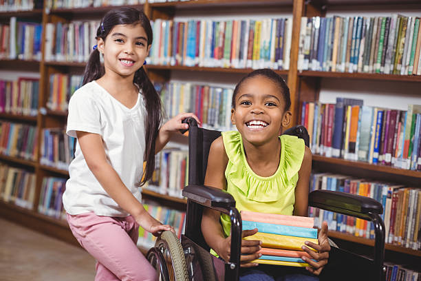 Smiling pupil in wheelchair holding books Portrait of smiling pupil in wheelchair holding books in the library in school paraplegic stock pictures, royalty-free photos & images