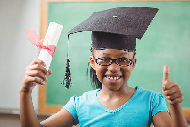 Smiling pupil with mortar board doing thumbs up stock photo