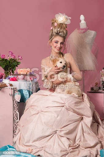 istock Smiling queen Marie Antoinette with dog in her lap 490938784