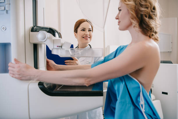 smiling radiologist standing near patient while making mammography diagnostics on x-ray machine stock photo