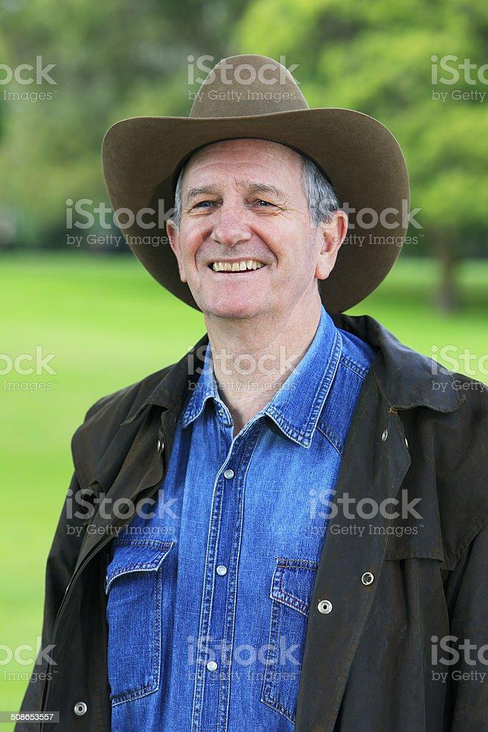 Smiling rancher in bush hat and waterproof coat stock photo