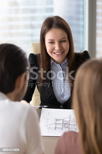 istock Smiling realtor presenting plan of two-story building, house for sale 689401658