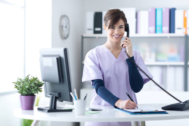 smiling receptionist at the clinic - nurse on phone stock photos and pictures