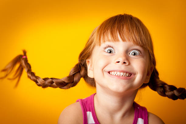Smiling Red-Haired Girl with Upward Braids and Excited Look stock photo
