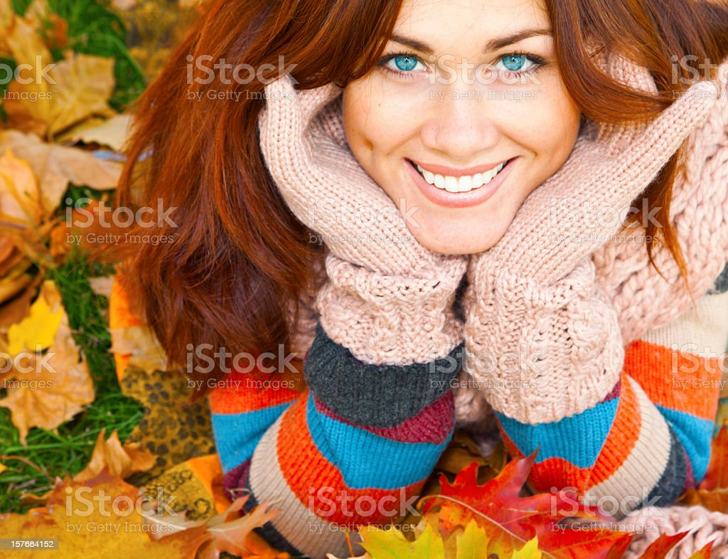Smiling red-haired woman laying on autumn leaves royalty-free stock photo
