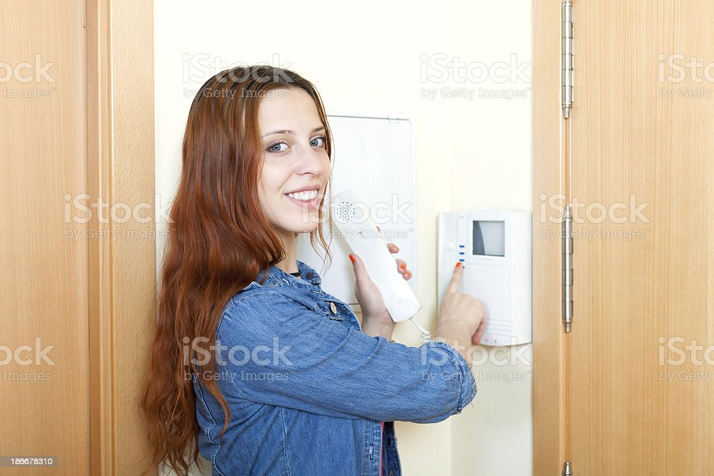 Smiling red-haired young woman talking on the house videophone stock photo