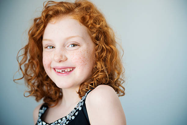 Smiling redhead little girl with freckles and missing tooth. Portrait of a smiling little girl with flamboyant redhead and a missing tooth. She has curly hair and is looking at the camera. Light gray background. Focus on one eye. Horizontal indoors head and shoulders shot with copy space. This was shot in Quebec, Canada. 8 9 years stock pictures, royalty-free photos & images