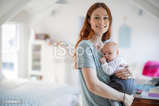 Smiling redhead woman standing with cute son. Portrait of beautiful mother is carrying newborn baby boy in bedroom. They are at home.