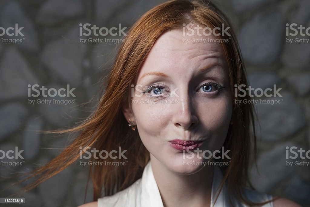 Smiling redhead woman outdoors against stone wall headshot royalty-free stock photo