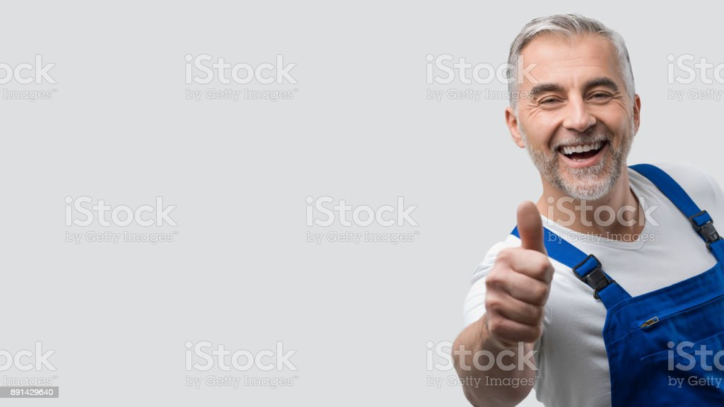 Smiling repairman giving a thumbs up stock photo