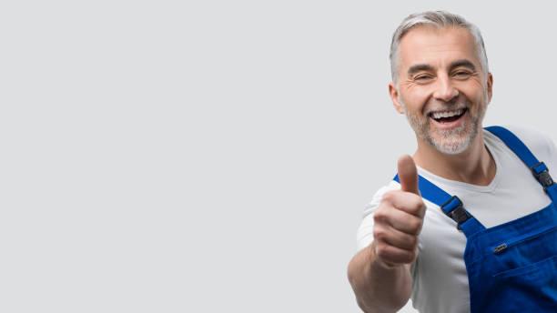 reparador sorridente dando um polegar para - consertador - fotografias e filmes do acervo