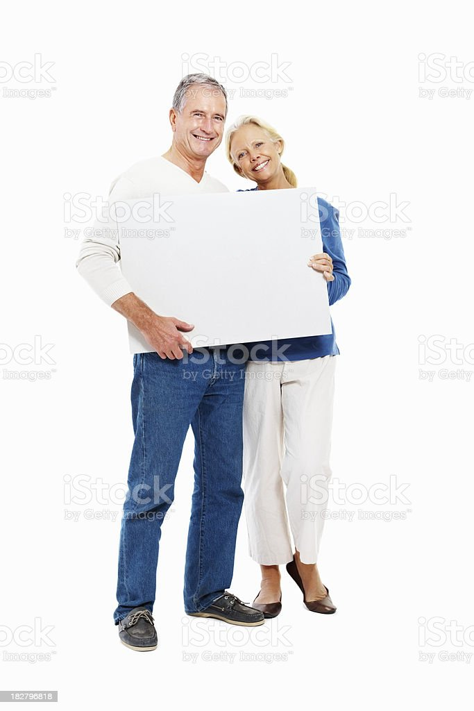 Smiling retired couple holding a blank billboard royalty-free stock photo