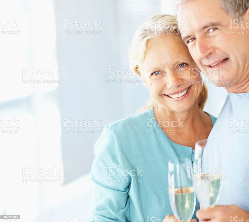 Smiling retired couple holding champagne glasses royalty-free stock photo