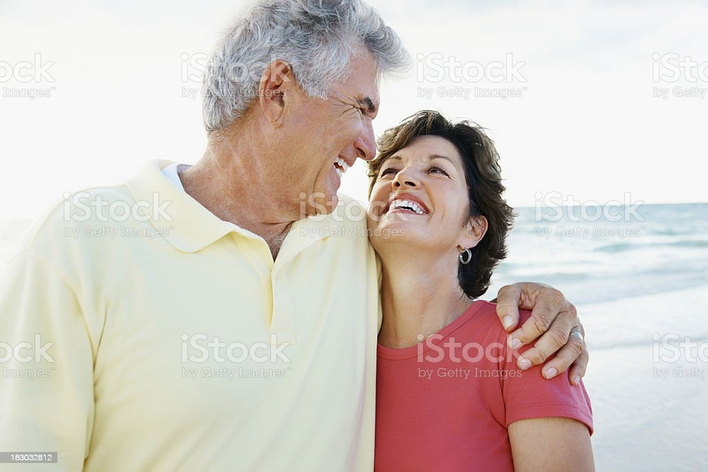 Smiling retired couple with arms around at a beach royalty-free stock photo