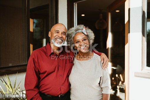 Portrait of retired man standing with arm around wife at front yard. Smiling senior couple is against house. They are in casuals.