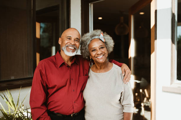 Smiling retired man standing with arm around wife stock photo