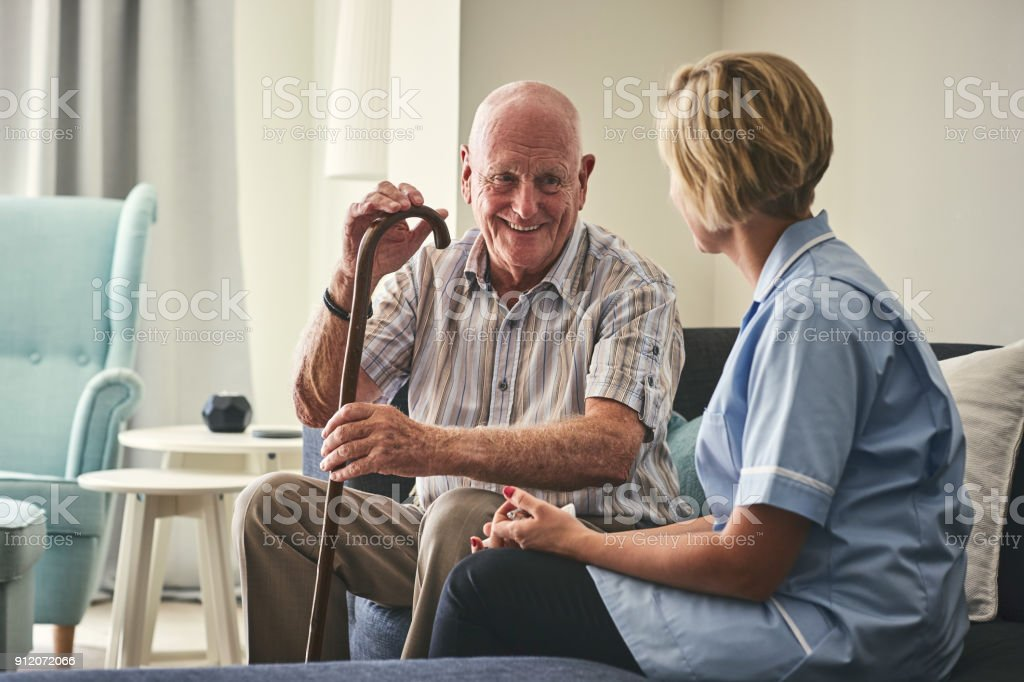 Smiling retired man with female home carer stock photo