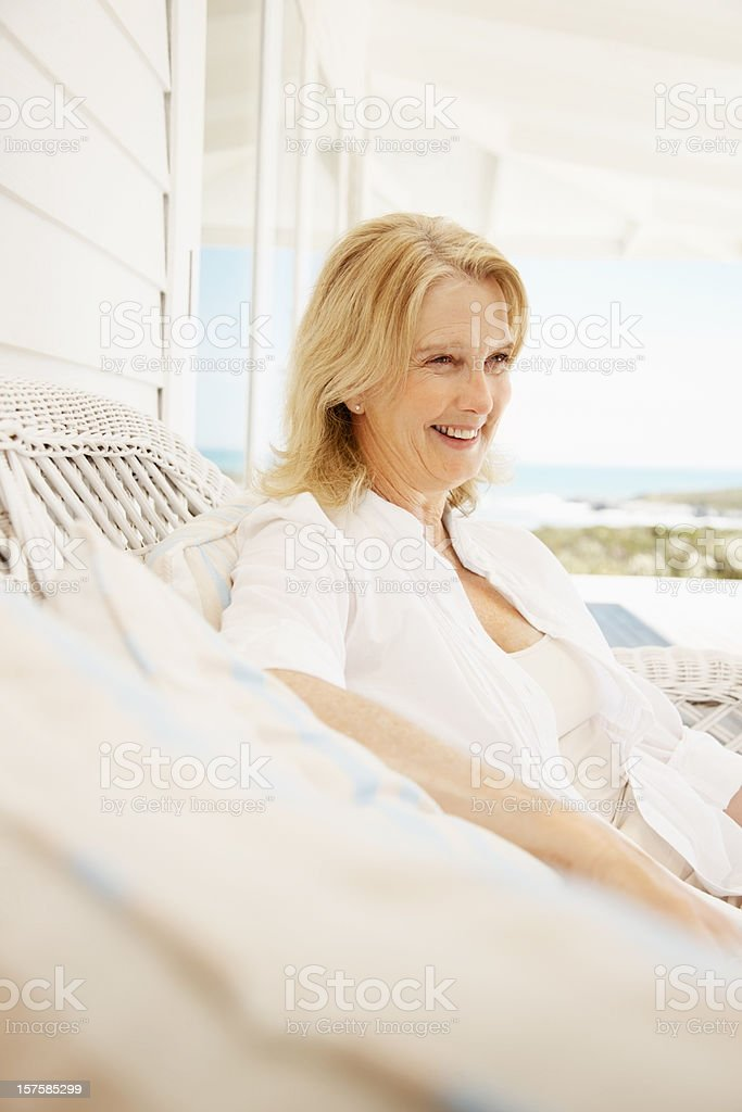 Smiling retired woman sitting on a couch at the porch royalty-free stock photo