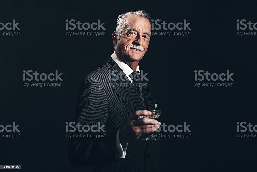 Smiling retro 1940s senior businessman holding champagne glass. stock photo
