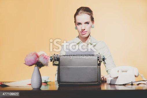 istock Smiling retro 1950 blonde secretary woman sitting behind desk wo 477109522