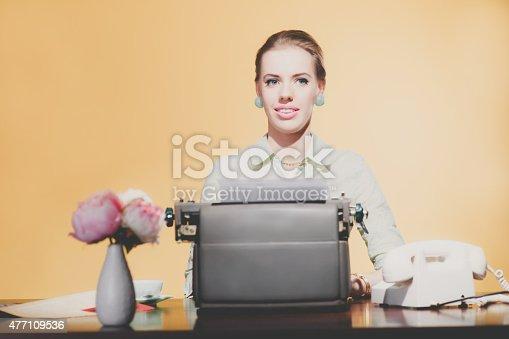 istock Smiling retro 1950 blonde secretary woman sitting behind desk wo 477109536