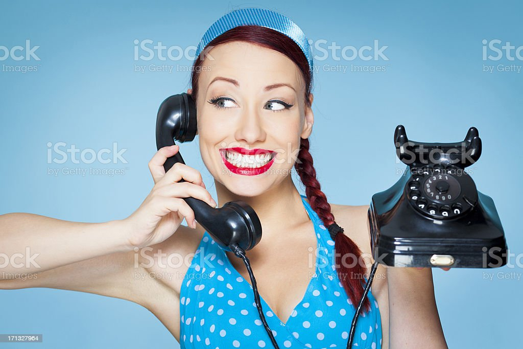 Smiling Retro woman with plaited hair holding old telephone royalty-free stock photo