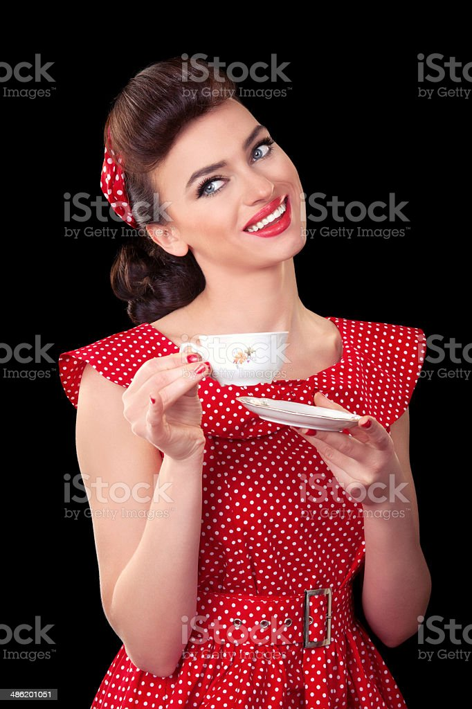 Smiling retro young woman with cup of coffee or tea stock photo