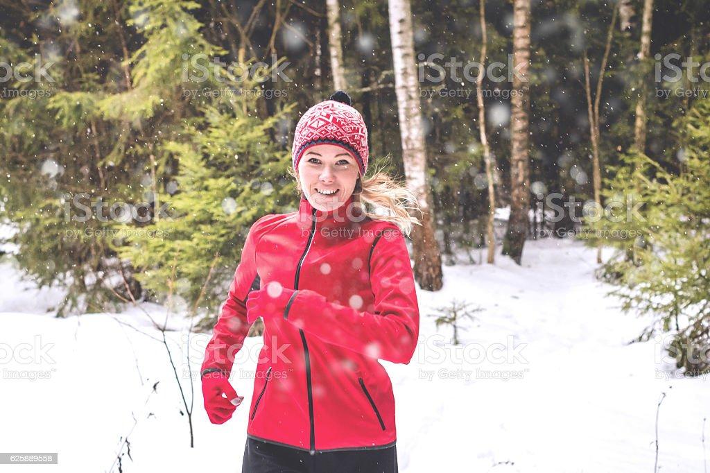 Smiling runner in winter forest stock photo
