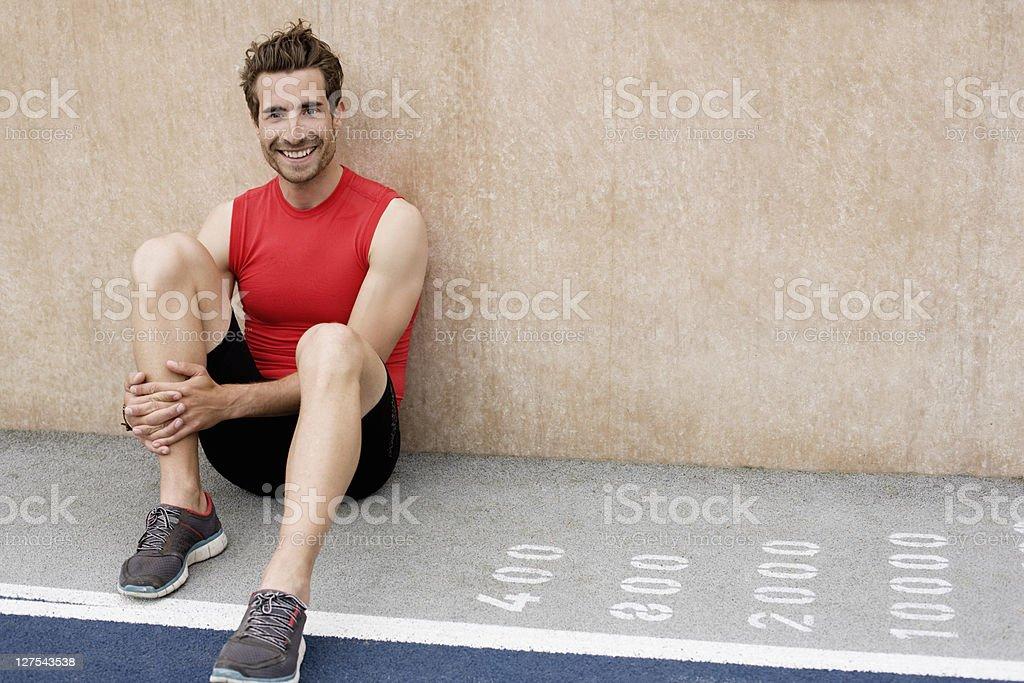 Smiling runner sitting against wall stock photo