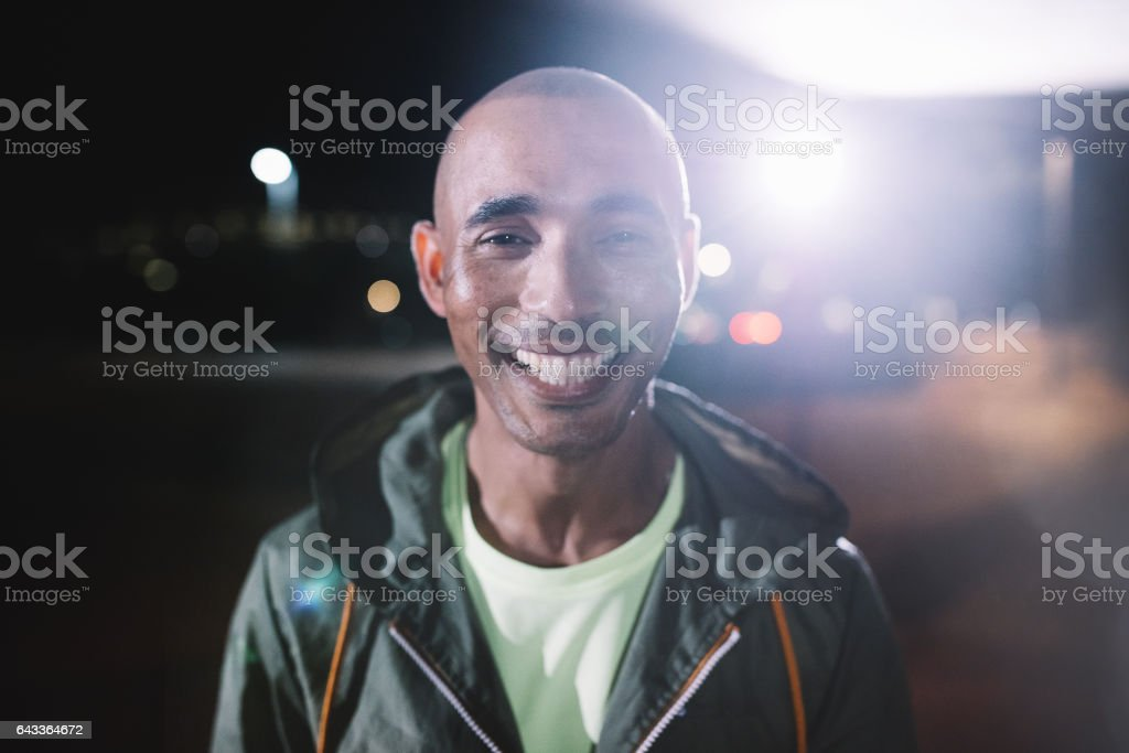 Smiling runner standing in city at night – Foto