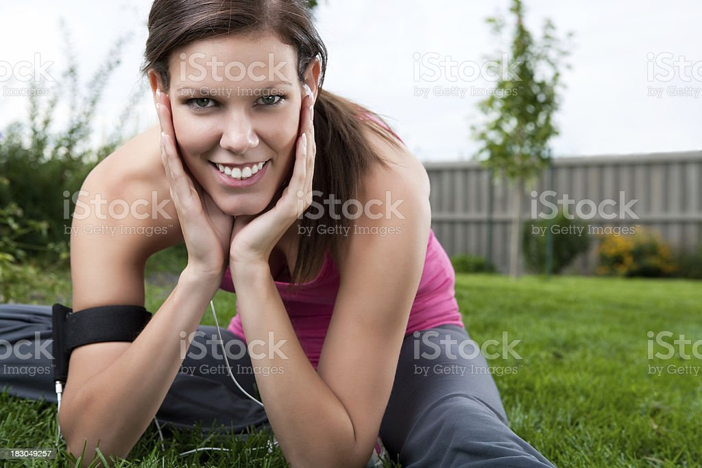 Smiling runner stretching on grass royalty-free stock photo