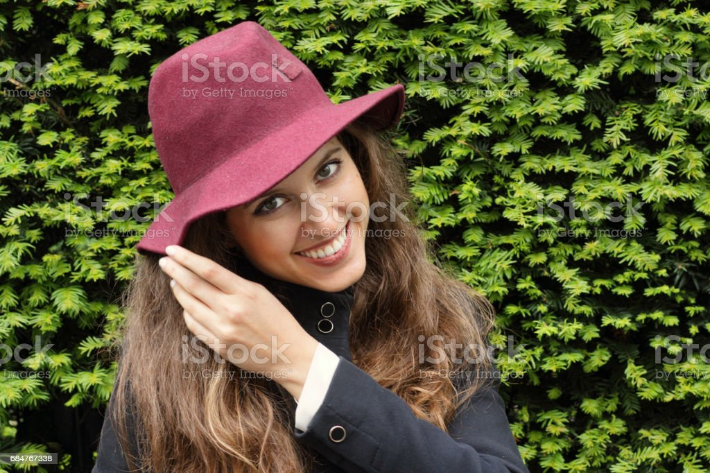 Smiling Russian outdoor girl adjusts felt hat fashion stock photo