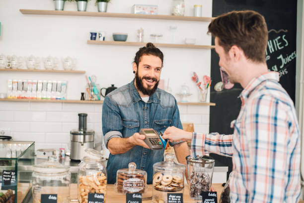 Smiling sales man assisting customer in credit card purchase Young man paying with credit card market vendor stock pictures, royalty-free photos & images