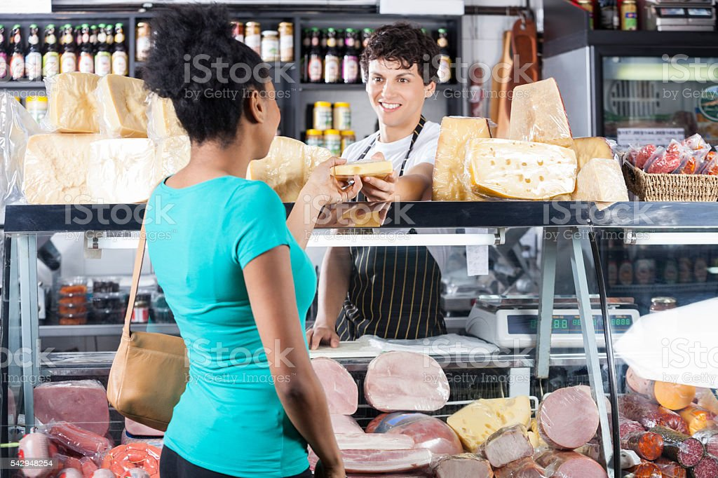Smiling Salesman Selling Cheese To Female Customer - foto de acervo