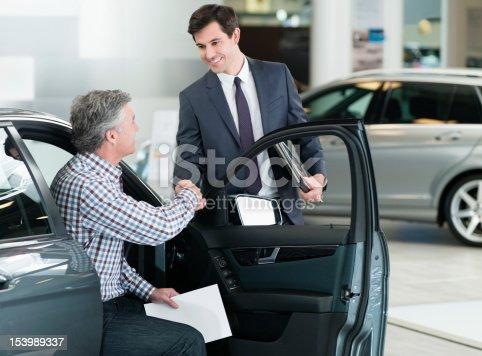 istock Smiling salesman shaking manÕs hand in car dealership showroom 153989337