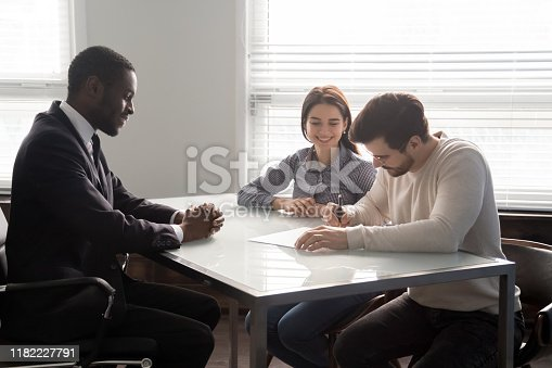 istock Smiling salesman watching happy clients signing contract. 1182227791