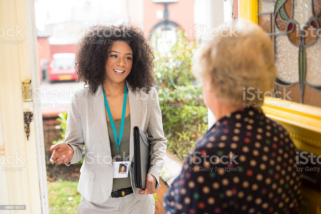 Smiling saleswoman or housing official chats at the door stock photo