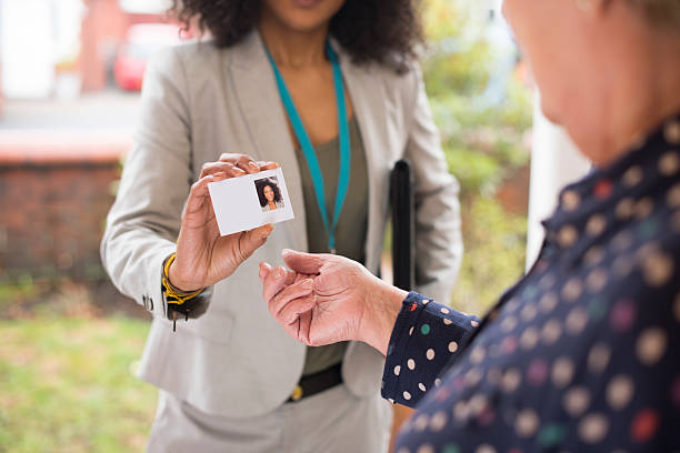 smiling saleswoman presents her card at the door . - identity card stock photos and pictures