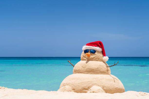 Lächelnder Sandschneemann mit rotem Santa-Hut am karibischen Strand. Urlaubskonzept für Neujahrs- und Weihnachtskarten – Foto
