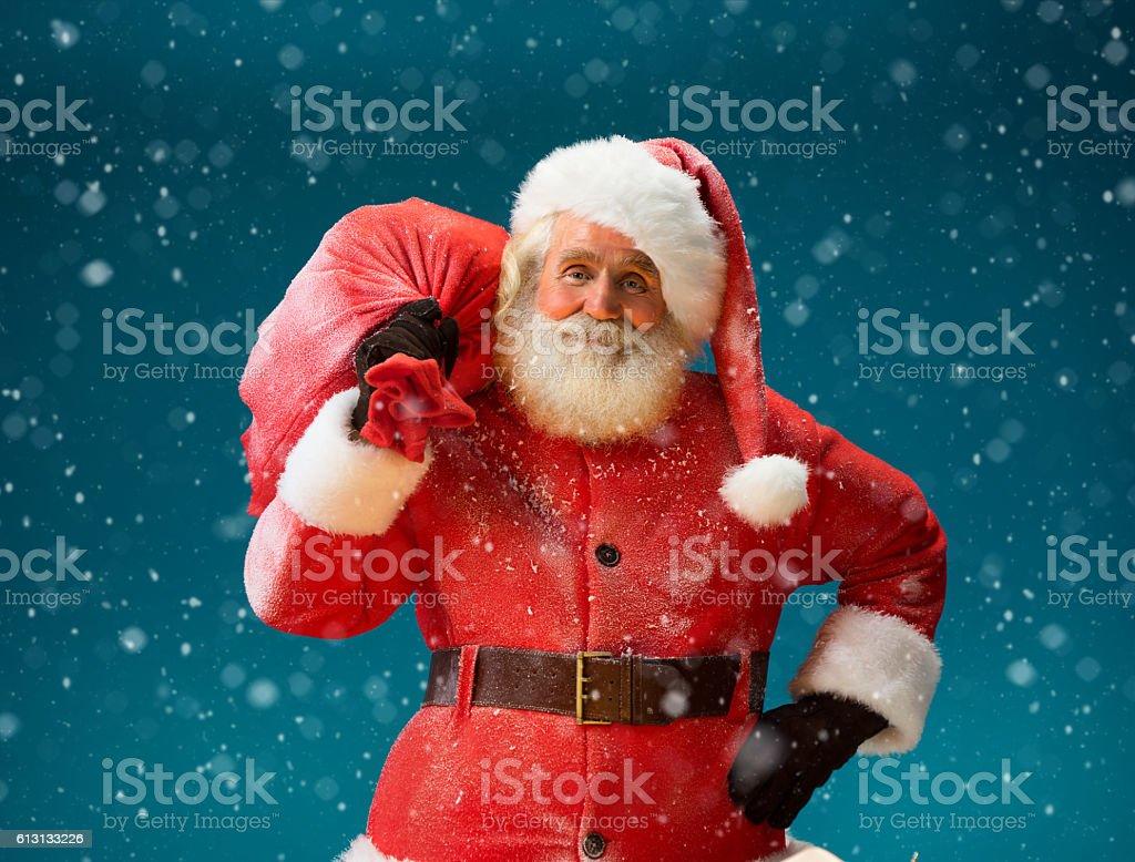 Smiling Santa Claus carrying big bag full of gifts stock photo