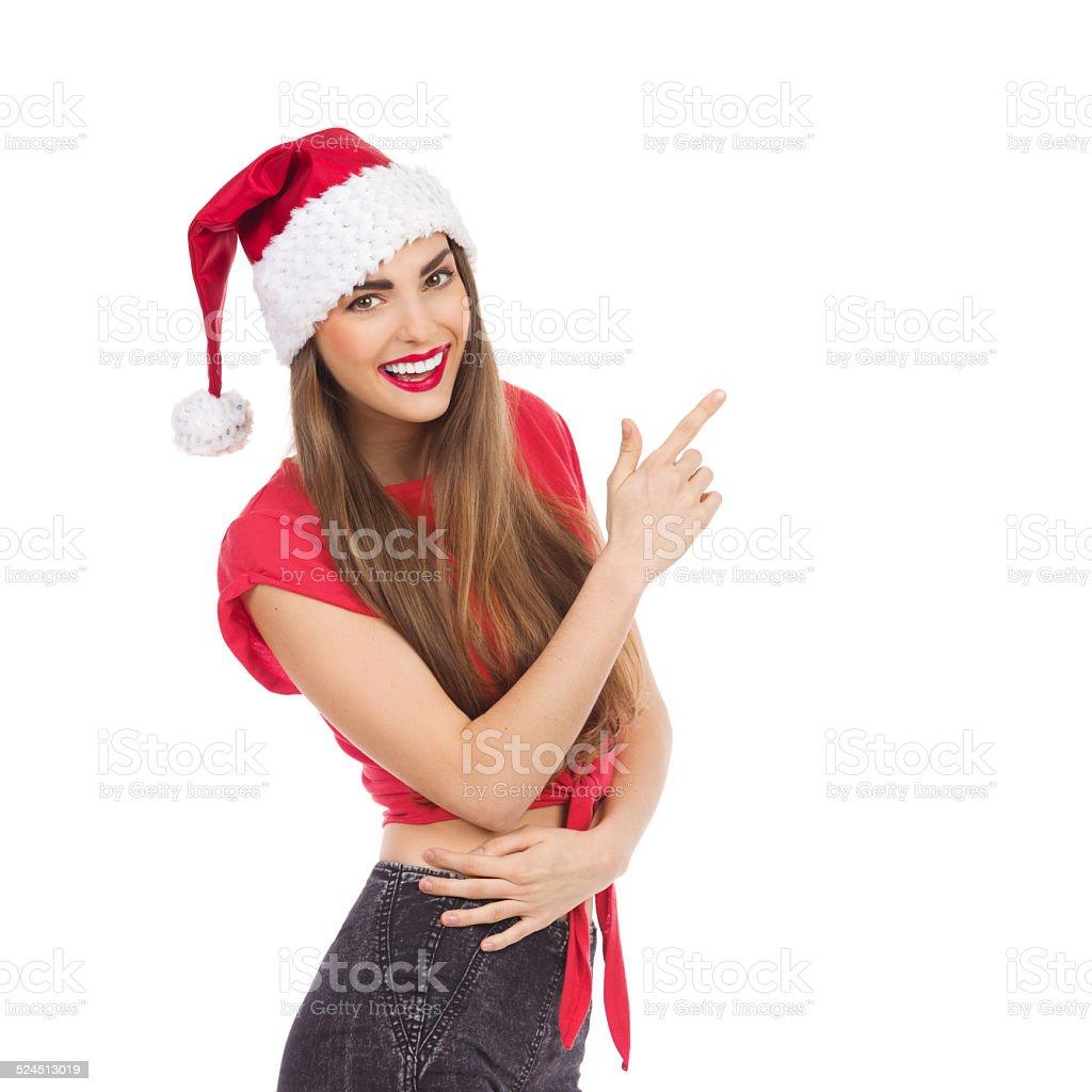 Smiling Santa girl pointing stock photo