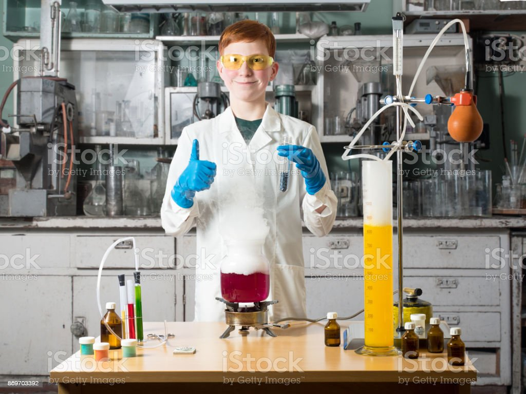 Smiling school boy holds a test tube in his hand stands in a white robe beside chemical table and holds in hands of the flask on a background of chemical laboratory with table and chemical equipment stock photo