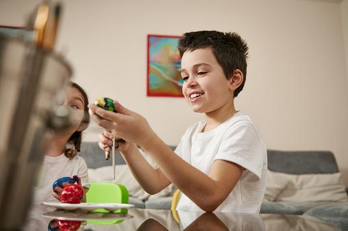 Smiling school boy in white t-shirt enjoying decorating Easter eggs