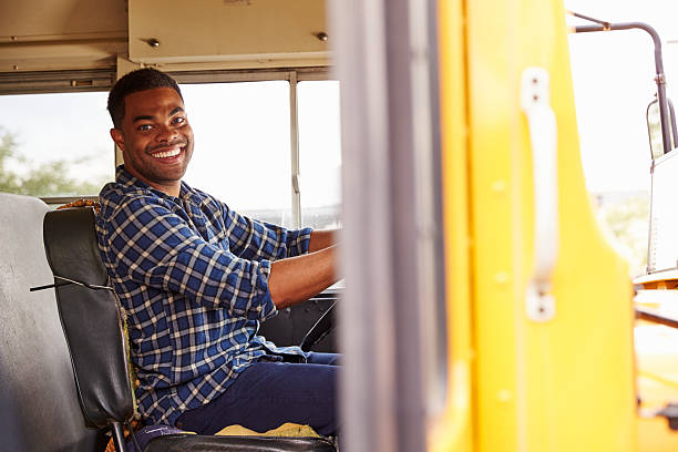 Smiling school bus driver sitting in bus stock photo