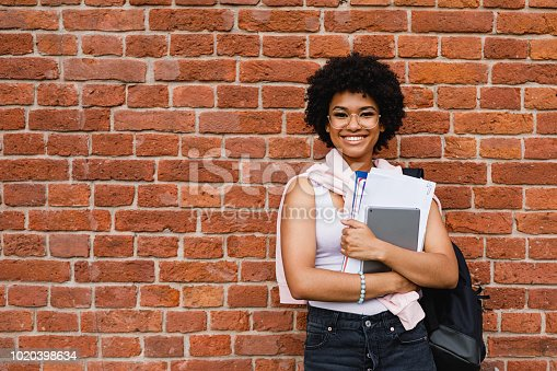 Smiling school girl with books standing at building wall