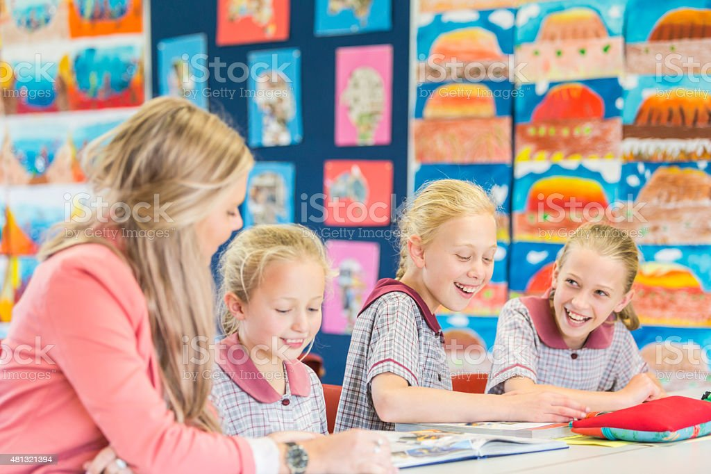 Smiling School Girls Laughing and Learning in the Classroom stock photo