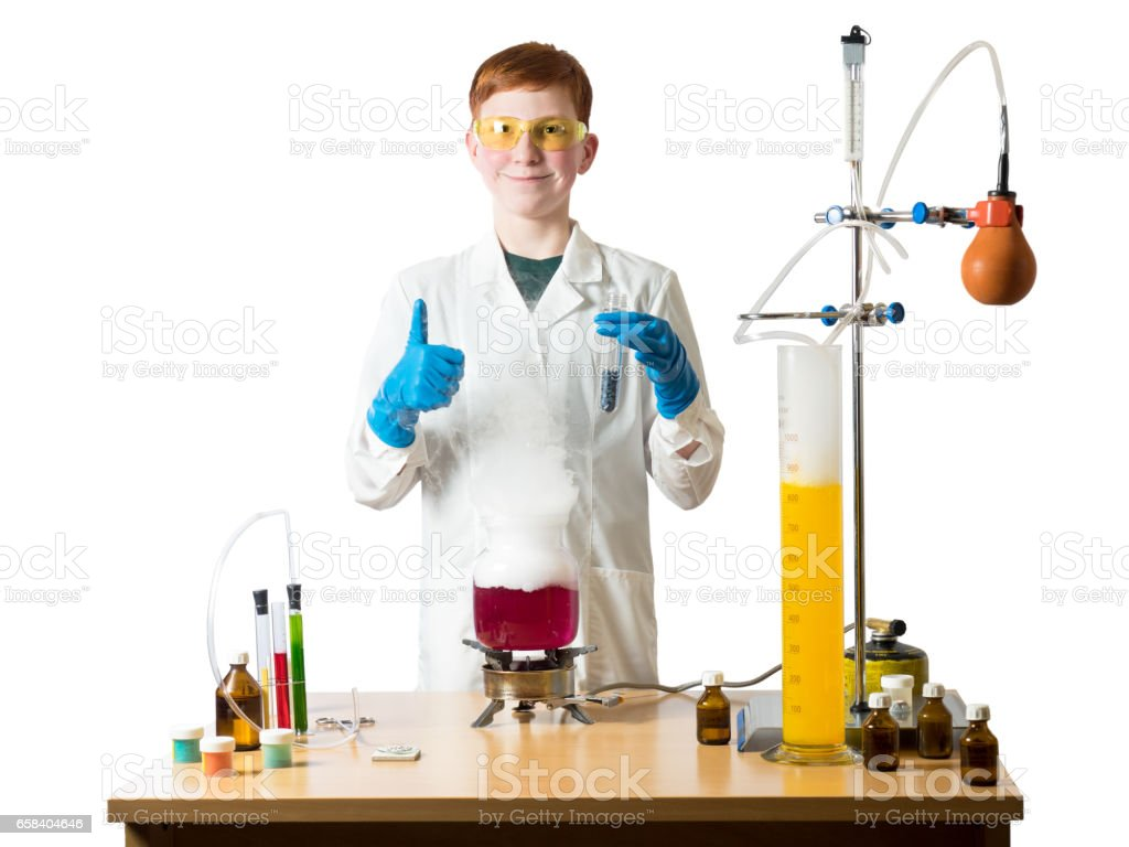 Smiling schoolboy holds a test tube in his hand stands in a white robe beside chemical table and holds in hands of the flask in the background laboratory equipment stock photo