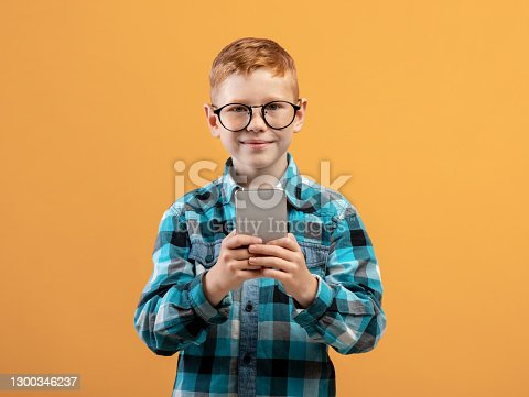 Smiling boy schooler playing game or using amazing application on smartphone over yellow studio background, copy space. Happy ginger kid in glasses using newest mobile phone, entertainment concept