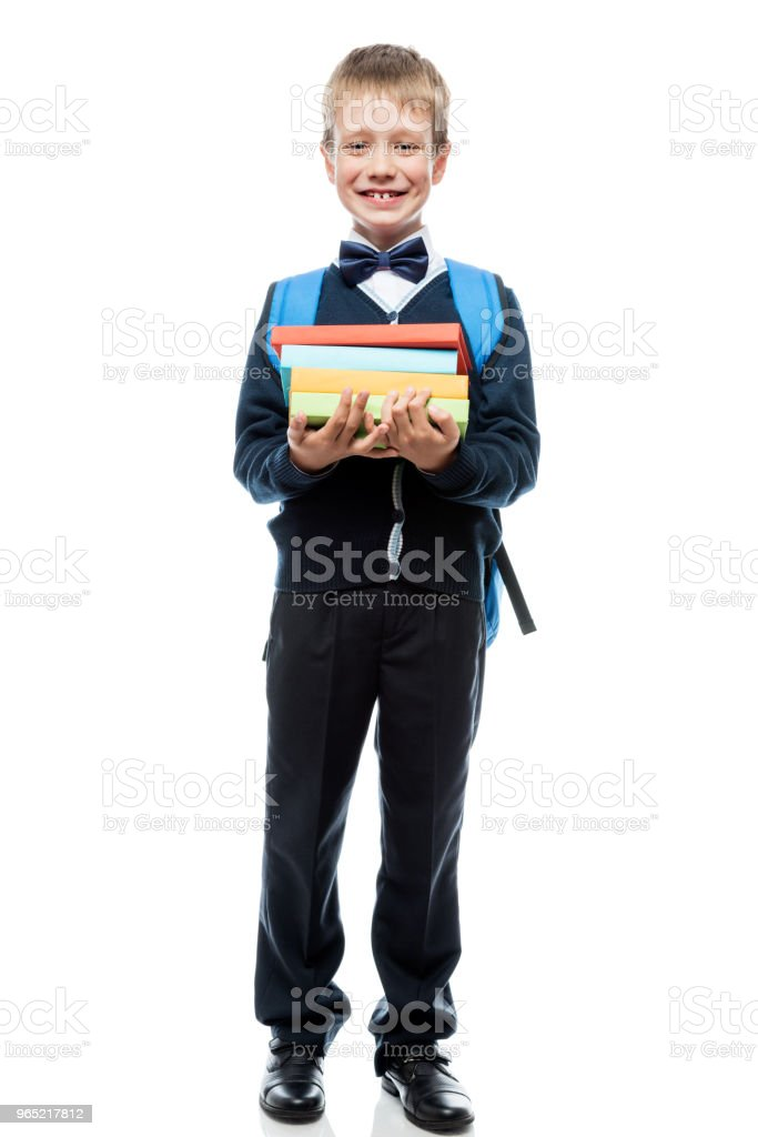 smiling schoolboy posing against white background, portrait is isolated in full length royalty-free stock photo
